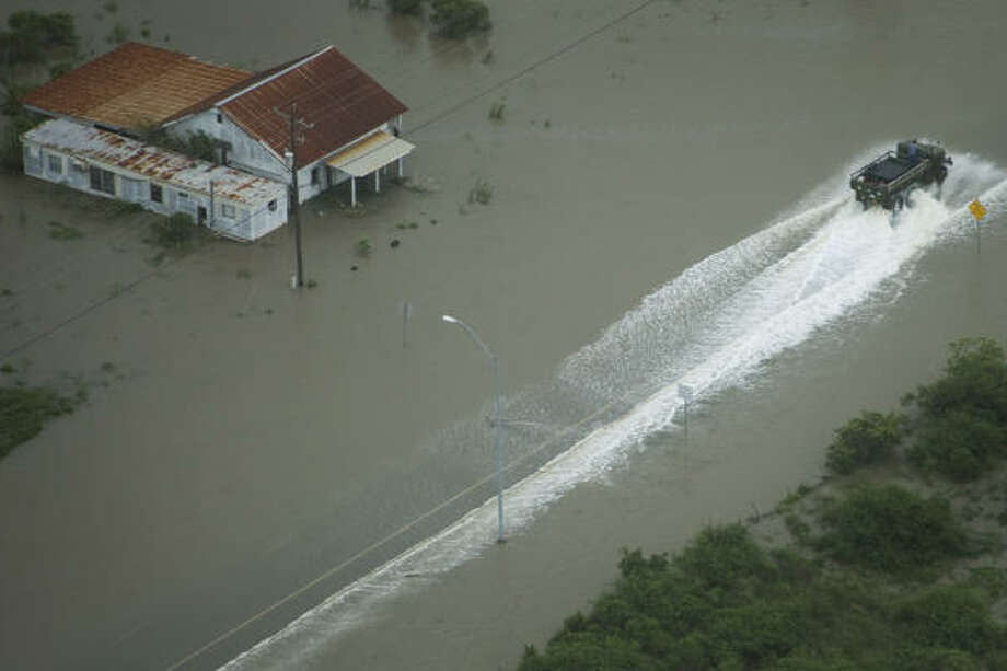 Leaving a wake  A truck maneuvers through floodwaters.   Sept. 12   Bolivar Peninsula Photo: Smiley N. Pool, Houston Chronicle