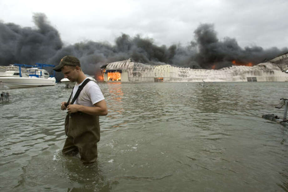 Flames| Chase Griffin walks through floodwaters after checking on a boat storage facility that caught fire. | Sept. 12 | Galveston Photo: Brett Coomer, Houston Chronicle