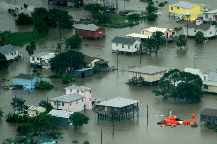 Flyover | A Coast Guard helicopter passes above homes threatened by rising waters. | Sept. 12 | Bolivar Peninsula Photo: Smiley N. Pool, Houston Chronicle