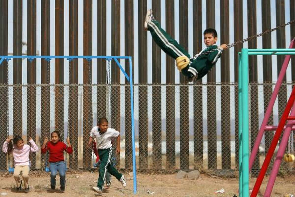 Fifteen-foot-high girders of a newly completed segment of the U.S. border fence abut a school playground in Palomas, Mexico, across the line from Columbus, N.M.