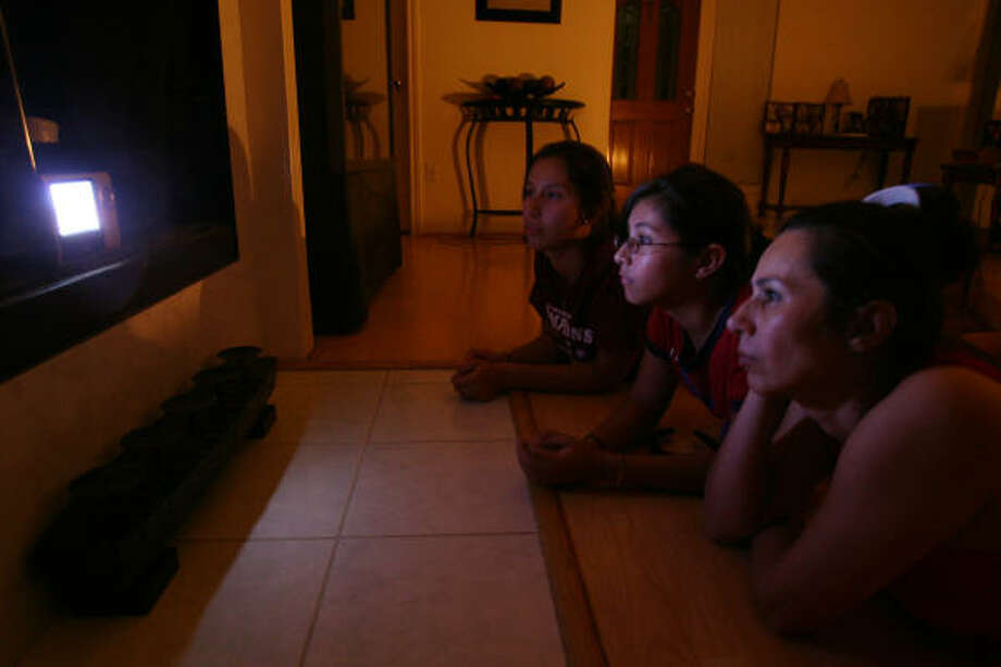 In the dark | The Longorias - sisters Ingrid and Lisa, and their mother Lorena - watch a battery-operated TV after the power goes out at their home. | Sept. 12 | Pearland Photo: Mayra Beltran, Houston Chronicle