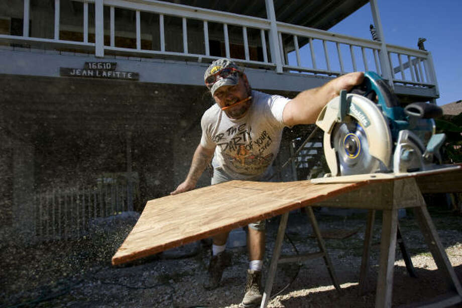 Preparation | Robert Sawyer cuts plywood to board up a home. | Sept. 10 | Jamaica Beach Photo: Johnny Hanson, Houston Chronicle