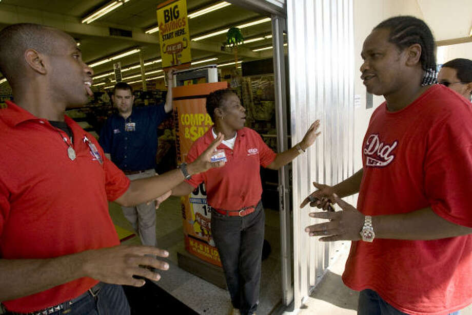 "Closing early | HEB employees tell Victor Arthur, right, that the store already closed. ""What am I supposed to do about food?"" Arthur asked. ""I guess I'll try the corner store."" 