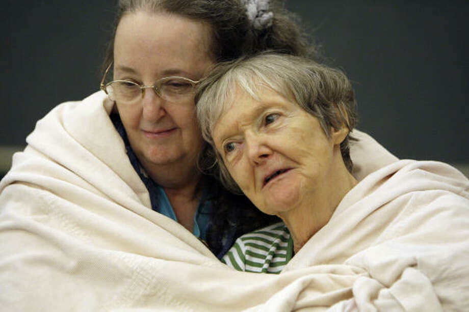 Family ties | Carole McFadden, left, and her mother, Freda Evans, try to stay warm as they wait to be evacuated by bus from a staging site at Charles T. Doyle Convention Center. | Sept. 11 | Texas City Photo: Melissa Phillip, Houston Chronicle