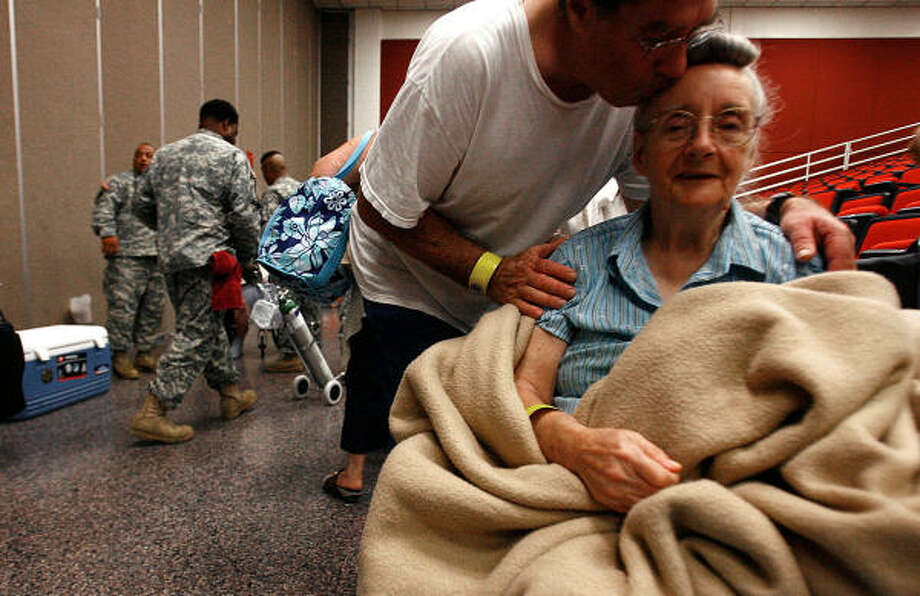A kiss for the road | Pearl Newman, 79, gets a kiss from her son-in-law, Phil Walters, while waiting to be evacuated by the National Guard at the Pasadena Convention Center. | Sept. 11 | Pasadena Photo: Sharon Steinmann, Houston Chronicle