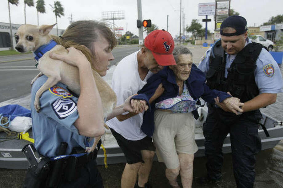 To safety | Galveston police officer Jeremy Smart, right, and Chris Hendricks, center, assist 93-year-old Belle Kenney from a rescue boat. Police Sgt. Renaye Ochoa holds a dog, Pete, who belongs to another resident. | Sept. 12 | Galveston Photo: Melissa Phillip, Houston Chronicle