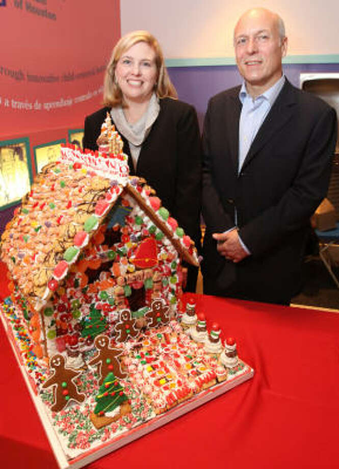 Caroline Mitchell and Manolo Sanchez admire a gingerbread house created by chef Michael Lieb during the Children's Museum Houston's Home Sweet Home Gingerbread Bash. Photo: Bill Olive, For The Chronicle