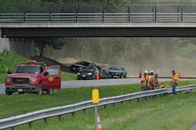 Workers cut away the guardrail on the Thruway so that stopped drivers can cross the median to the eastbound lane between exits 23 and 24 during a gas main break on Wednesday, Aug. 10, 2011, in Guilderland, NY. Airborne debris can be seen in the air from the break,  just beyond the bridge in the background, at left.  (Philip Kamrass / Times Union) Photo: Philip Kamrass / 00014226A