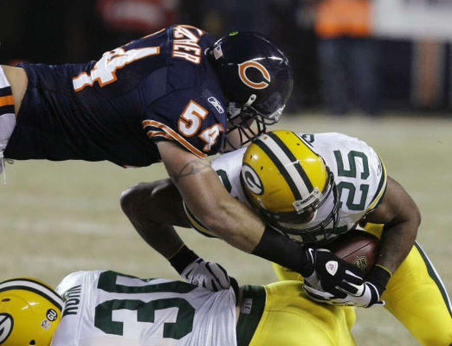 Bears 20, Packers 17 (OT) Bears linebacker Brian Urlacher, left, flies over Packers fullback John Kuhn to tackle running back Ryan Grant during the first quarter. Photo: Charles Rex Arbogast, AP