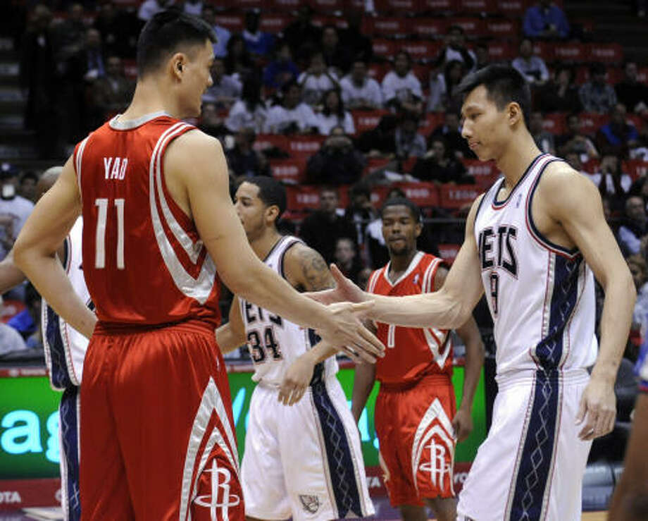 Rockets center Yao Ming, left, and New Jersey Nets forward Yi Jianlian, both of China, shake hands before the opening tip of Monday night's game in East Rutherford, N.J. Yao finished with a game-high 24 points, 16 rebound and four blocks in the Rockets' 114-91 win. Yi had 10 points and seven rebounds. Photo: Bill Kostroun, AP