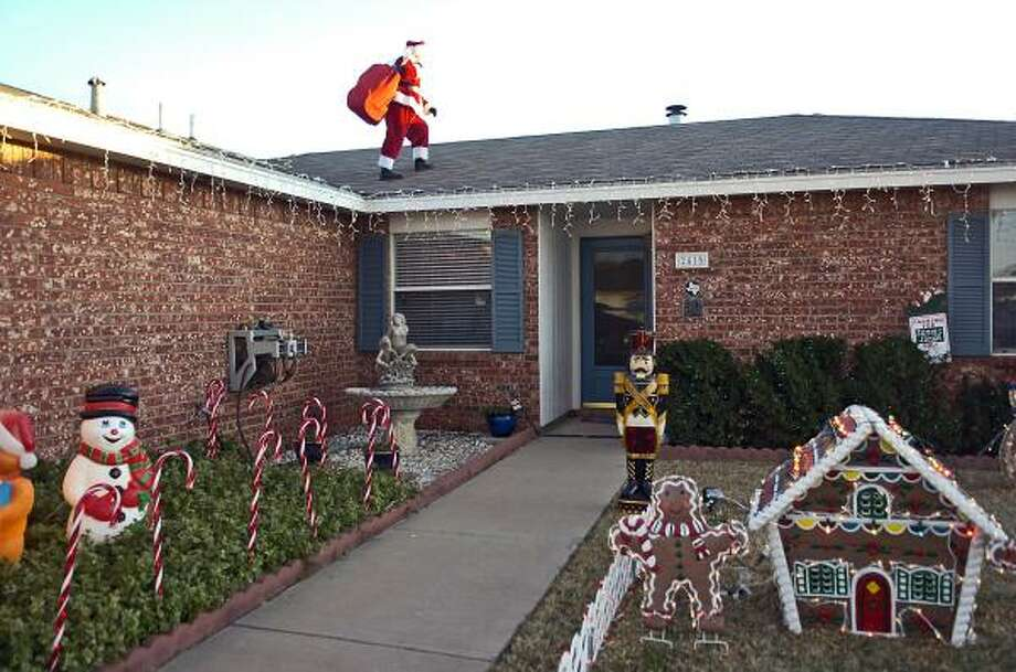 IN TEXASDennis Hargrove walks on a rooftop in dressed as Santa Claus in Lubbock. The former Lubbock Independent School District principal spends about five weeks every year in the boots and red-and-white fur-trimmed suit, reading stories to children and handing out candy canes from Thanksgiving until the day after Christmas. Photo: Geoffrey McAllister, AP