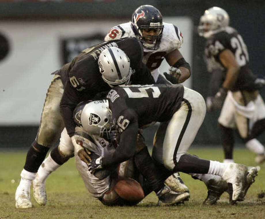 Texans quarterback Matt Schaub Raiders defensive end Derrick Burgess (56) and defensive tackle Gerard Warren (61) in the Raiders' 27-16 win, which snapped Houston's four-game win streak. Photo: Brett Coomer, Chronicle