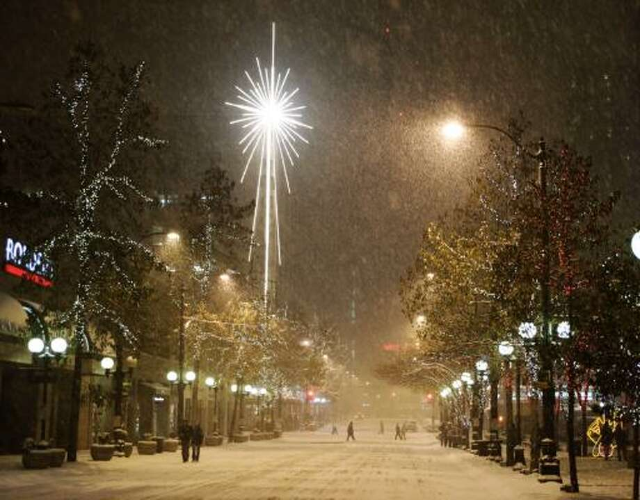 A giant star on a Macy's store shines as heavy snow falls late Saturday night in downtown Seattle. Very few cars were on city streets at night, but there was heavy pedestrian traffic as people took in the sights and sounds of the winter storm. Photo: Ted S. Warren, AP