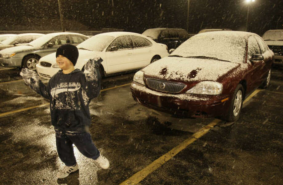 Mario Hernández Jr., de 6 años, juega con la nieve en la agencia de autos Affordable Cars & Trucks, ubicada en 5715 de la autopista I-45, donde trabaja su padre, Mario Hernández. Photo: Melissa Phillip, Houston Chronicle