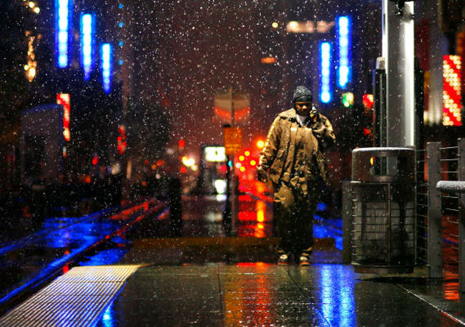 Tangela Jenkins camina hacia el tren mientras la nieve cae en la calle Main Street en el centro de Houston. Photo: Sharon Steinmann, Houston Chronicle