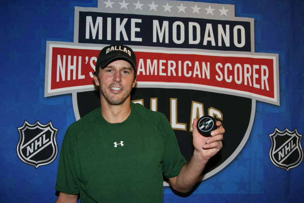 Dallas Stars center Mike Modano poses for pictures with his record-setting puck after becoming the all-time leading US-born scorer.