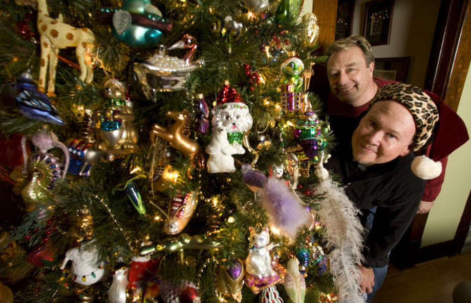 Michael Briden, left,  and Mike  Lowery pose beside the animal-themed tree in their Heights bungalow. Photo: Brett Coomer, Chronicle