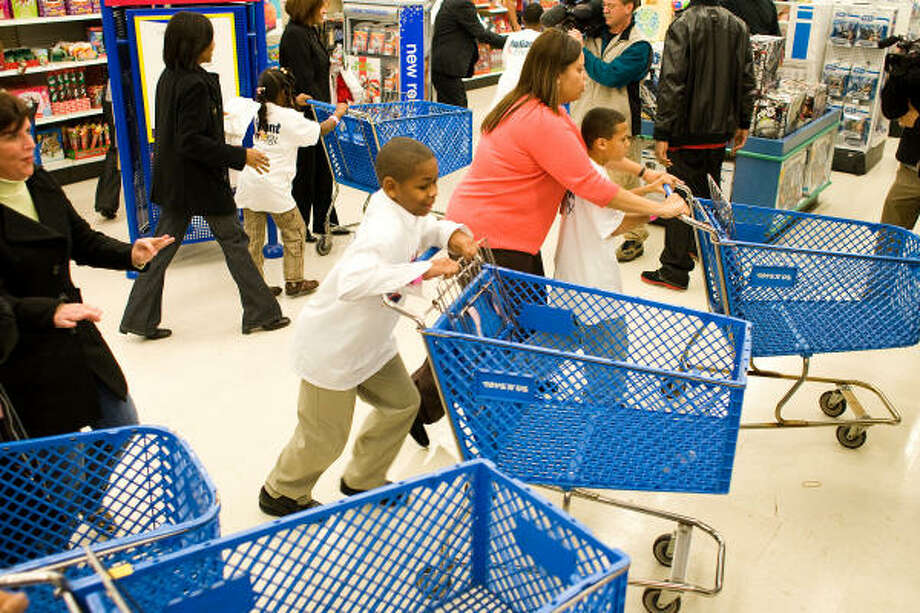 Ra'Shad Angel gets his shopping cart going as he and other kids were given 80 seconds to get what ever toys they want during the AJ Shopping spree at Toys R Us in Houston. Houston Texans receiver Andre Johnson payed the $16,000 bill. Photo: Nick De La Torre, CHRONICLE