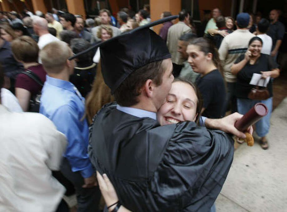 Josh Tladman, 23, left, receives a hug from his girlfriend Miki Schmidt, 22, after the Texas A&M Galveston fall graduation at the Moody Gardens Convention Center on Sunday in Galveston. Photo: Julio Cortez, Chronicle