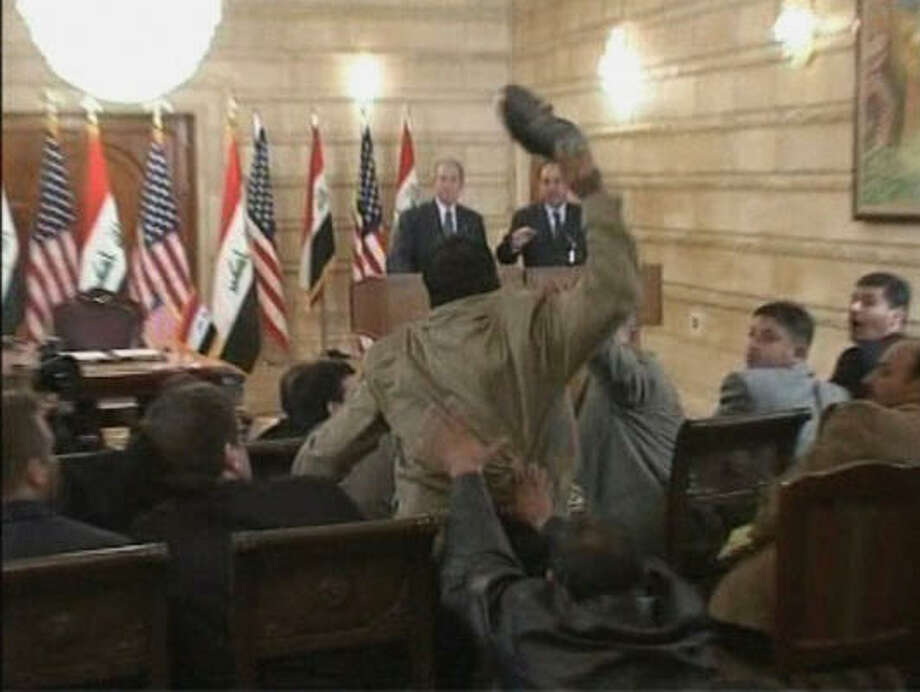In this image from APTN video, a man throws a shoe at George W. Bush during a news conference with Iraq Prime Minister Nouri al-Maliki Sunday in Baghdad. Photo: AP