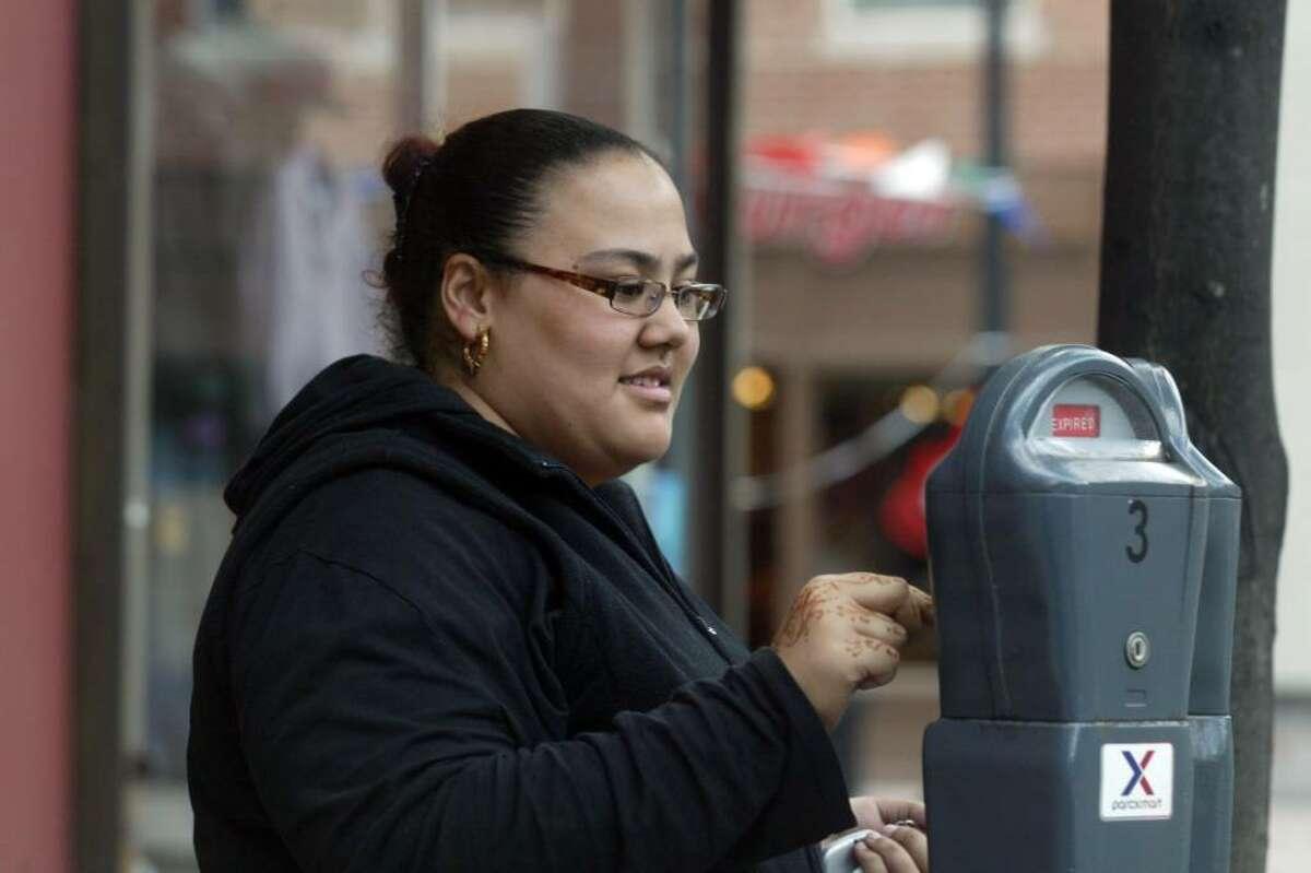 Maria Hernandez puts quarters in a meter on Arcade Street in downtown Bridgeport, Wednesday, Oct. 7, 2009.