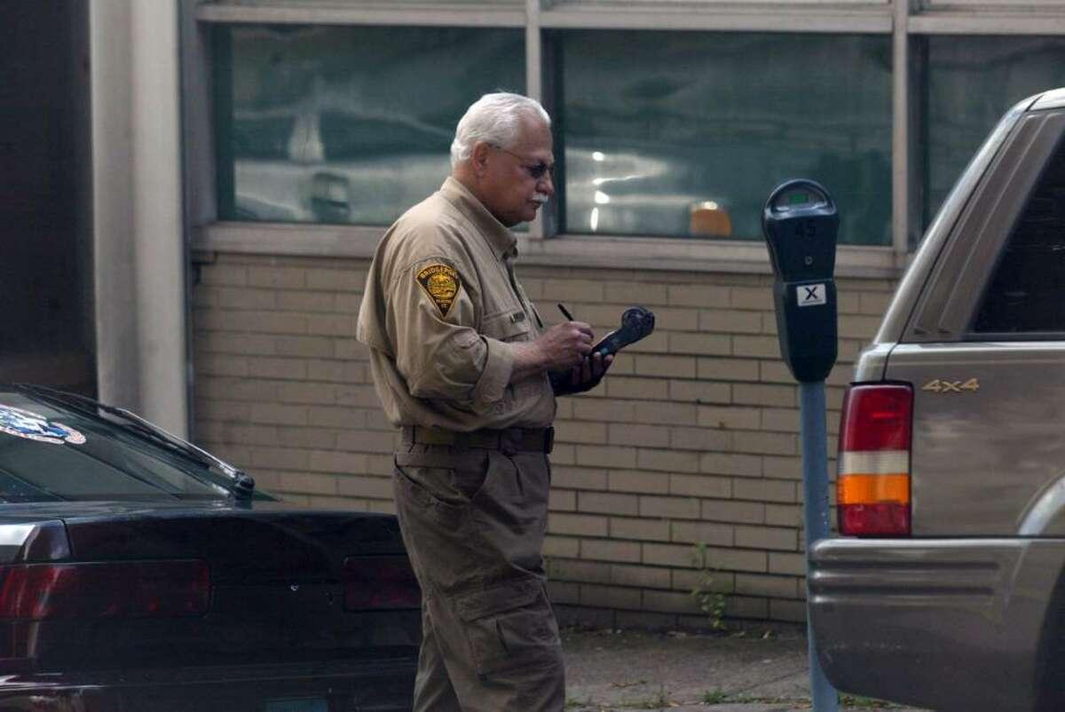A Bridgeport parking enforcement officer writes a ticket on Golden Hill Street, across from Superior Court, Wednesday, Oct. 7, 2009.