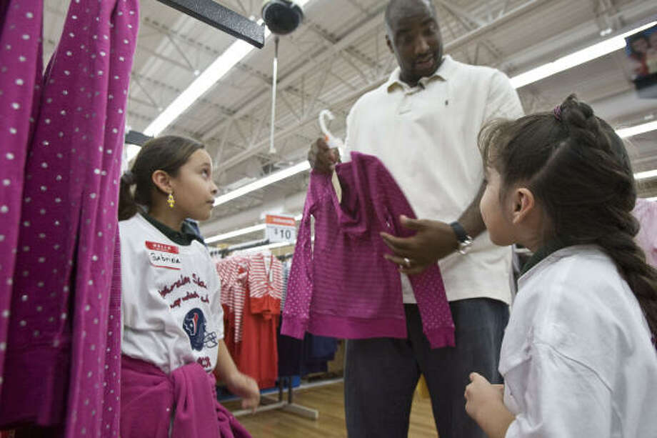 Texans offensive lineman Ephraim Salaam helps 10-year-old Gabriela Aguilar, left, and her sister Emaly Aguilar, 5, pick out pretty pink clothes Monday during his ''Shop with a Jock'' event at Wal-Mart. Photo: James Nielsen, Chronicle
