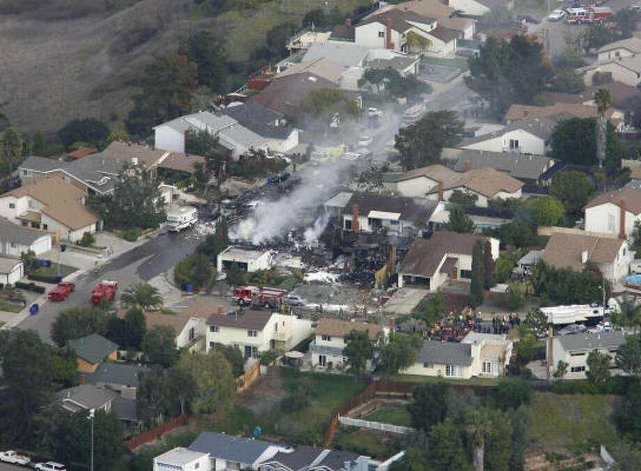 Smoke rises from a fire after an F-18 military jet crashed into a suburban neighborhood in San Diego on Monday. Photo: Denis Poroy, AP