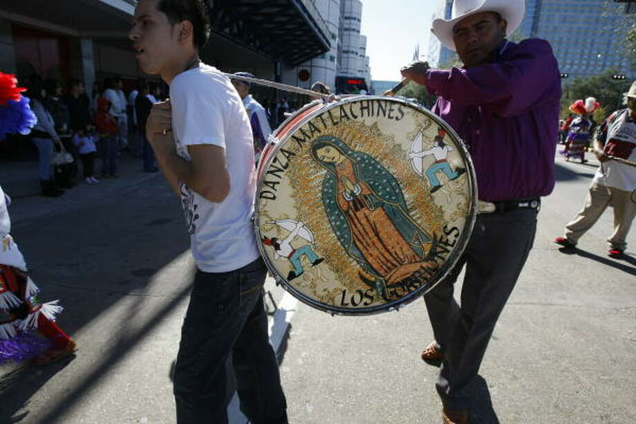 The image of Our Lady of Guadalupe is seen on the drum that led dancers during a pilgrimage walk around downtown toward the George R. Brown Convention Center on Sunday. Photo: Julio Cortez, Chronicle
