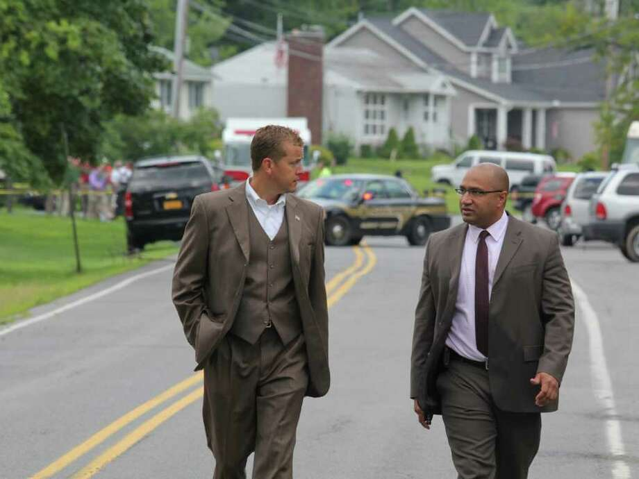 Acting Albany County Sheriff, Craig Apple, left, and Albany County Distric Attorney David Soares, right, walk down Mountain View Street past an accident scene in front of St. Matthew's Church, Voorheesville on Wednesday, Aug. 10, 2011. (Erin Colligan / Special To The Times Union)