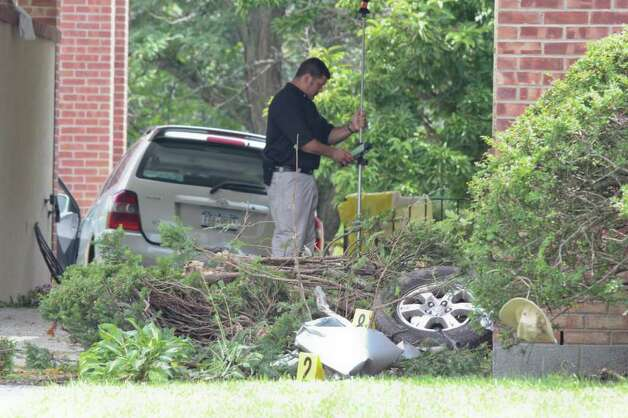 A law enforcement officer investigates a crash site at St. Matthew's church on Mountain View Street in Voorheesville on Wednesday, Aug. 10, 2011. The accident resulted in the deaths of three people. The driver alleges that her flip flop was caught under the accelerator of the car. (Erin Colligan / Special To The Times Union)