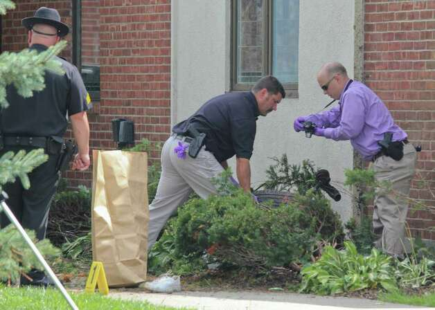 Law enforcement officers investigate a crash site at St. Matthew's church on Mountain View Street in Voorheesville on Wednesday, Aug. 10, 2011. The accident resulted in the deaths of three people. The front tire of the SUV was ripped from the car when it struck the corner of the church. (Erin Colligan / Special To The Times Union)
