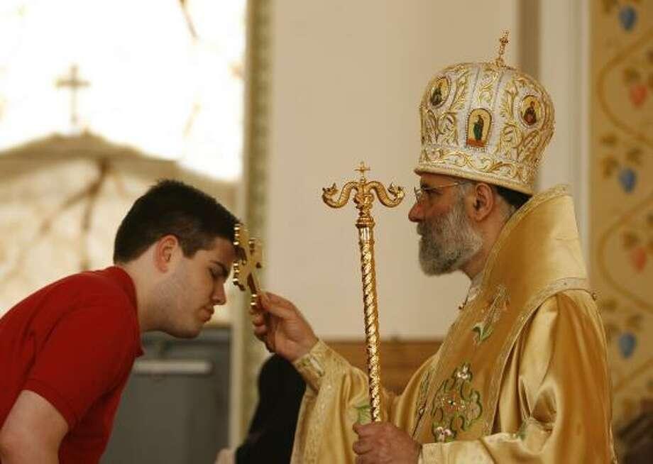 At Houston's St. George Antiochian Orthodox Christian Church, Metropolitan Saba blesses a parishioner in a recent service. Photo: JAMES NIELSEN, CHRONICLE