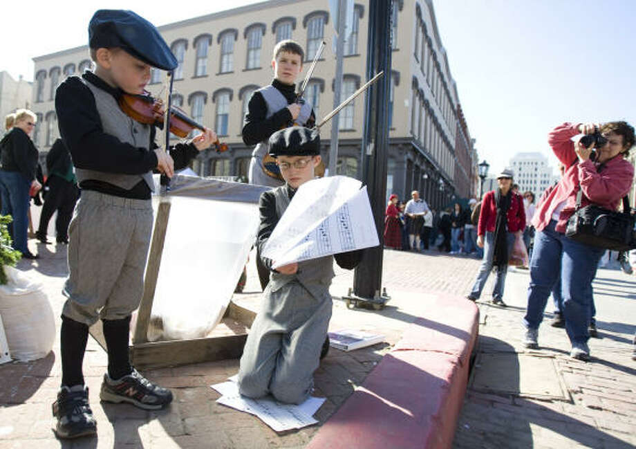 Travis Gibson, 5, of Nederland plays a Christmas Carol as his brother Jonas Gibson, 11, holds his music for him and his other brother Daniel Gibson, 14, waits during the Dickens on the Strand holiday festival in Galveston. Photo: Nick De La Torre, CHRONICLE
