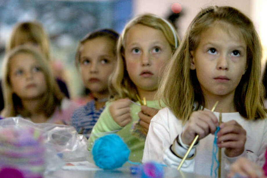 Holding their knitting needles, a group of Westwood Elementary School knitting club third graders knit newborn caps. Photo: Johnny Hanson, Chronicle
