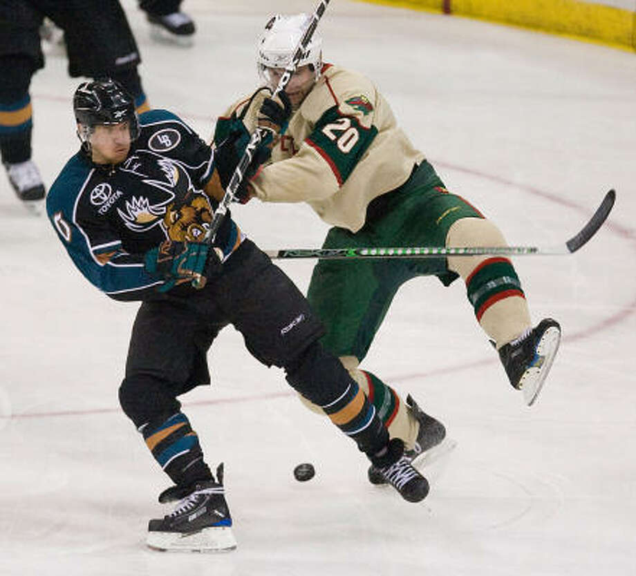Michael Grabner of the Manitoba Moose, left, and John Scott of the Aeros hustle for the puck in the second period on Thursday at Toyota Center. Photo: Nick De La Torre, CHRONICLE