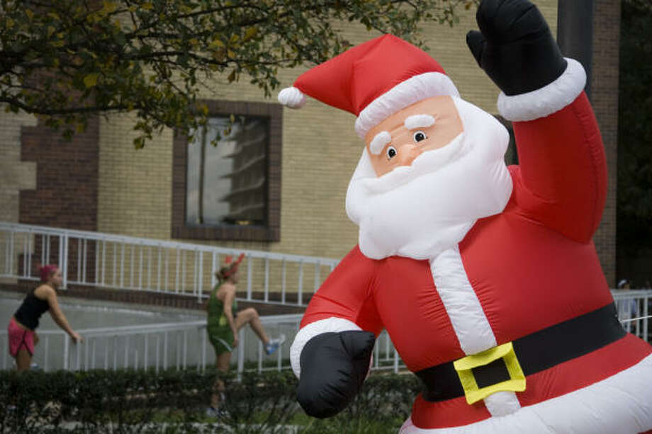 An inflatable Santa Claus greets runners as they stretch before the 24th Annual Chevron Jingle Bell Run and Walk benefiting the Downtown YMCA, Dec. 9, 2007. Photo: Smiley N. Pool, Chronicle