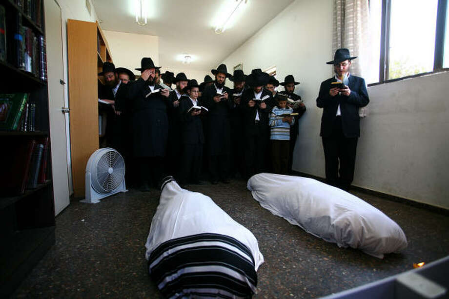 Ultra-Orthodox Jewish men and boys pray next to the bodies of Rabbi Gavriel Holtzberg and his wife, Rivka, at the start of the couple's funeral in Israel Tuesday. Photo: -, AFP/Getty Images