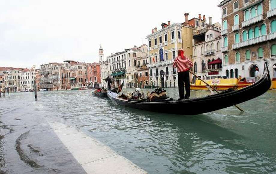 A gondola passes through floodwaters near the Rialto Bridge Dec. 2 in Venice. Photo: Franco Debernardi, Getty Images