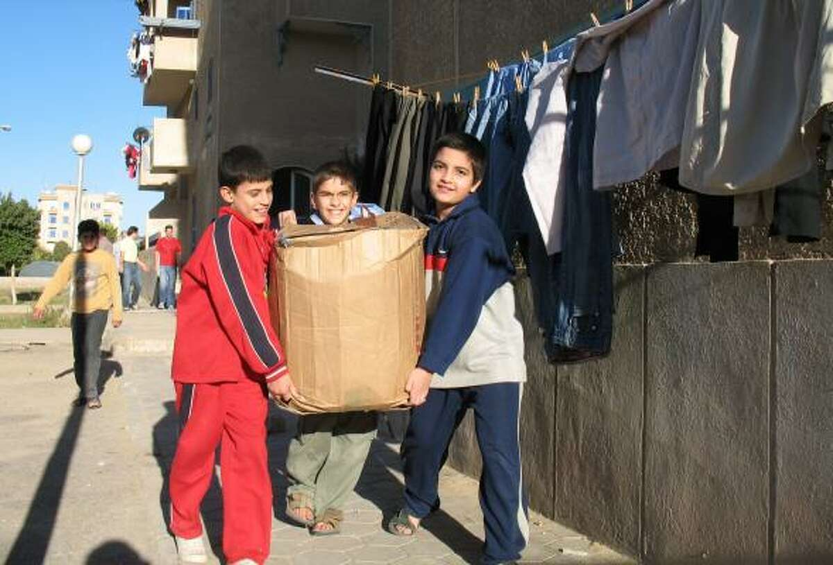 Iraqi boys carry a box of toys and clothes donated by a group of Americans trying to help the estimated 150,000 Iraqi refugees in Egypt. These boys live in Sixth of October City outside of Cairo.