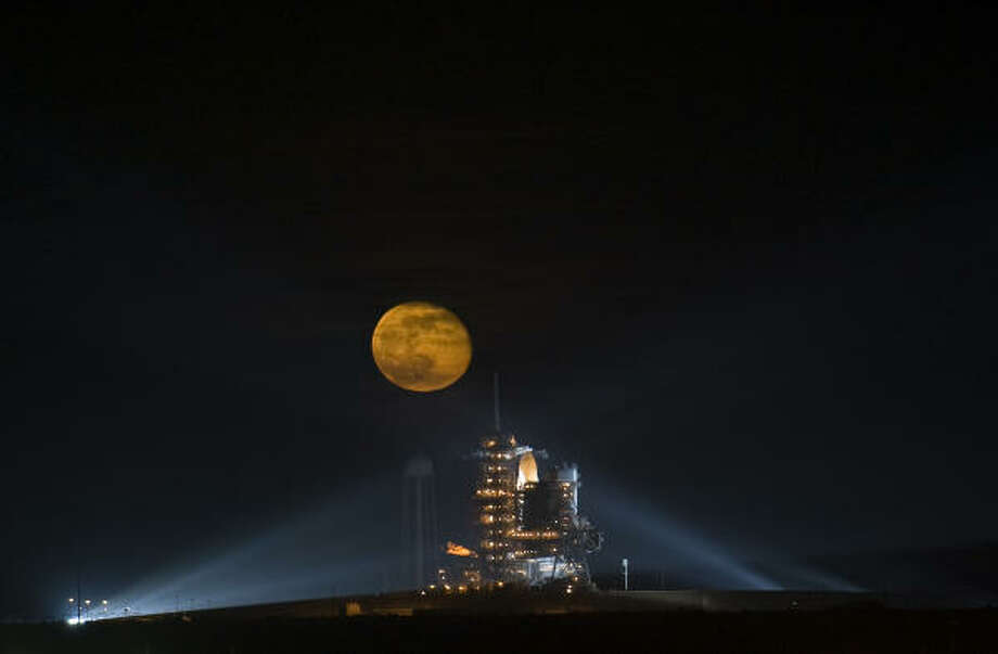 The moon rises behind the Space Shuttle Endeavour as it sits on pad 39A on Nov. 14 at the Kennedy Space Center in Cape Canaveral, Fla. Photo: NASA, Getty Images