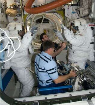 Attired in their spacesuits, astronauts Heidemarie Stefanyshyn-Piper (right) and Steve Bowen are pictured in the Quest Airlock of the International Space Station as the mission's first session of extravehicular activity Nov. 18 draws to a close. Astronauts Chris Ferguson (foreground, center), STS-126 commander, and Greg Chamitoff, mission specialist, assist with the doffing of the spacesuits. Photo: NASA, AP