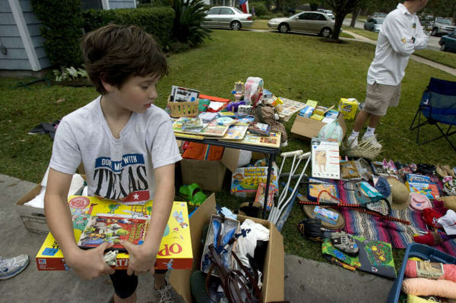 Ben Lux, 9, purchases a game and a book at a garage sale in the 3700 block of Gramercy. Photo: Johnny Hanson, Chronicle