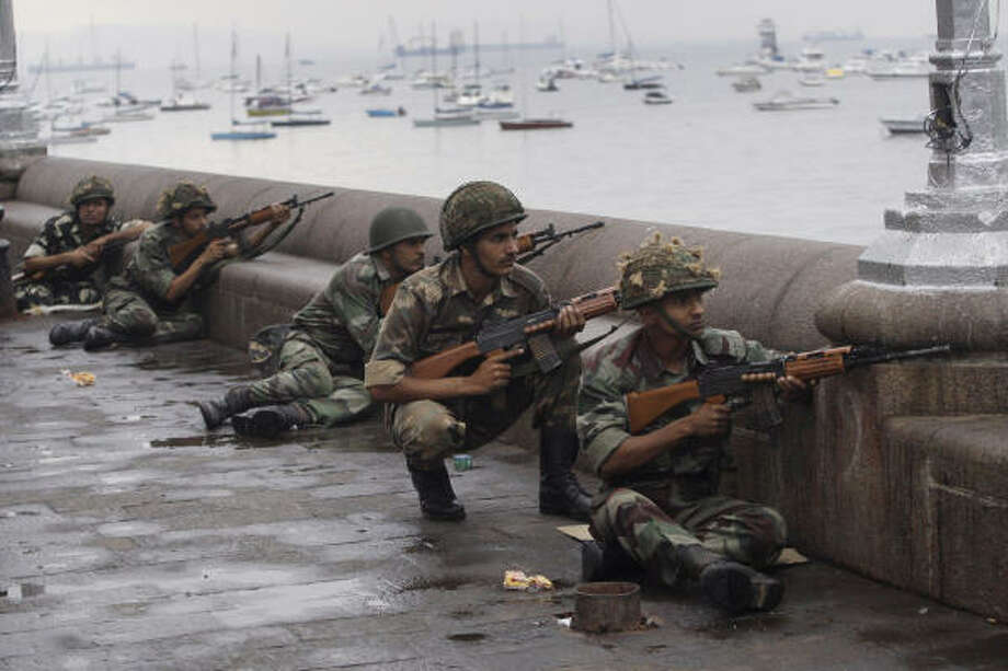 Indian soldiers take cover on the waterfront as they surround the Taj Mahal hotel during gun battles between Indian military and militants inside the hotel. Photo: David Guttenfelder, AP