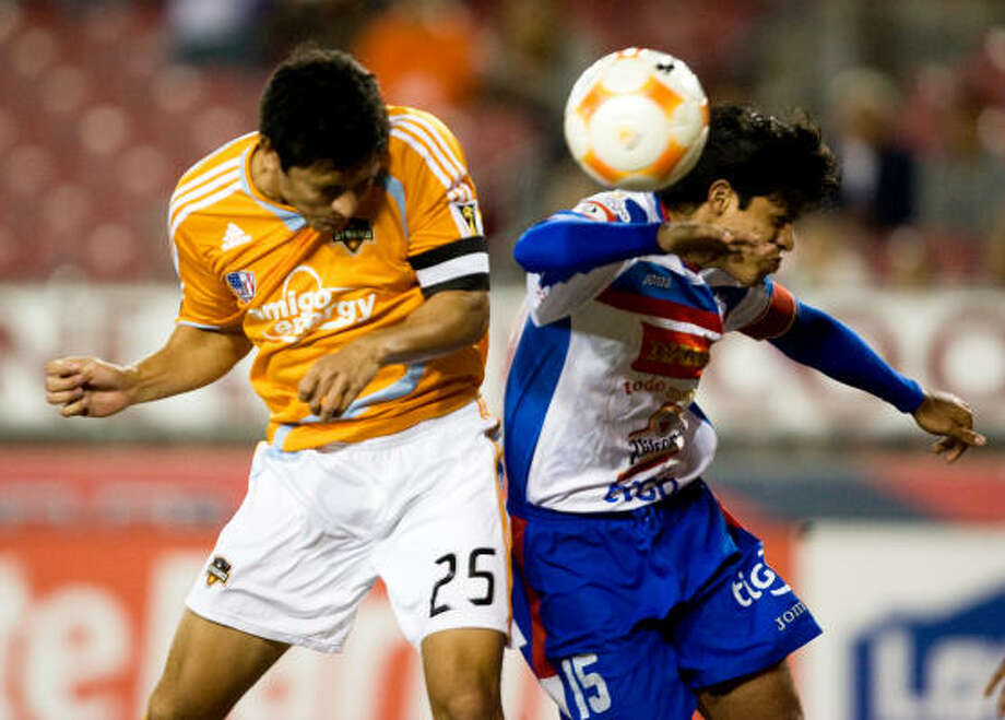 Dynamo forward Brian Ching, left, beats Luis Angel Firpo's Manuel Alejandro Salazar to a header to score a goal in the 13th minute of Wednesday's CONCACAF Champions League match at Robertson Stadium. The Dynamo won 1-0 to advance to the quarterfinals of the tournament. Photo: Bob Levey, For The Chronicle