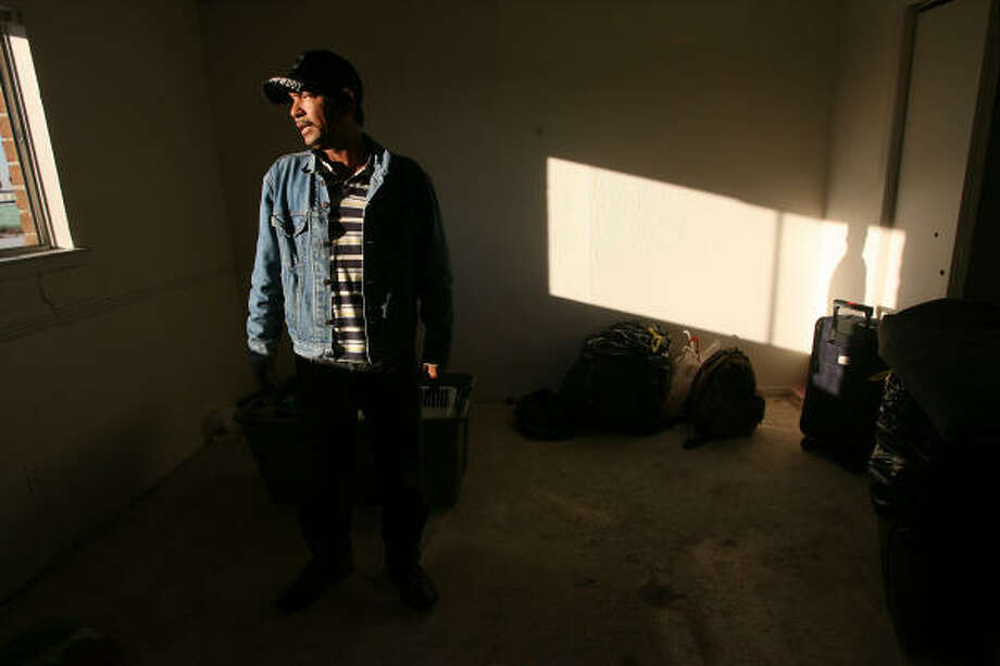 Francisco Parajon stands in a room with a broken window, no flooring, and a wrecked kitchen. He and five other men share an apartment and have no money to move out of the Vista Bonita apartment complex. Photo: Mayra Beltran, Chronicle