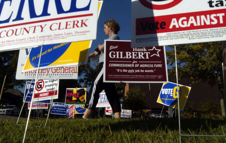 Kim Holz walks past groups of political lawn ads near the voting station at First Baptist Church Heights in Houston. Photo: Johnny Hanson, For The Chronicle