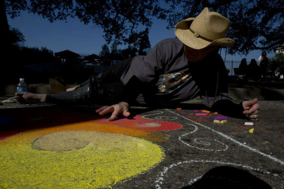 Jamie Mayes, of Houston, puts finishing touches on an original artwork at the Via Colori festival. The event's proceeds benefited the Center for Hearing and Speech, which teaches children with hearing loss to speak rather than use sign language. Photo: Johnny Hanson, Chronicle