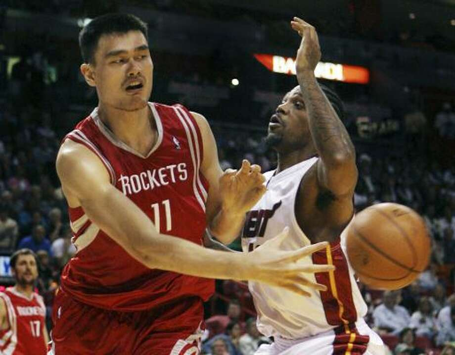 Yao Ming passes around Heat center Udonis Haslem in the first quarter. Photo: Jeffrey Boan, AP