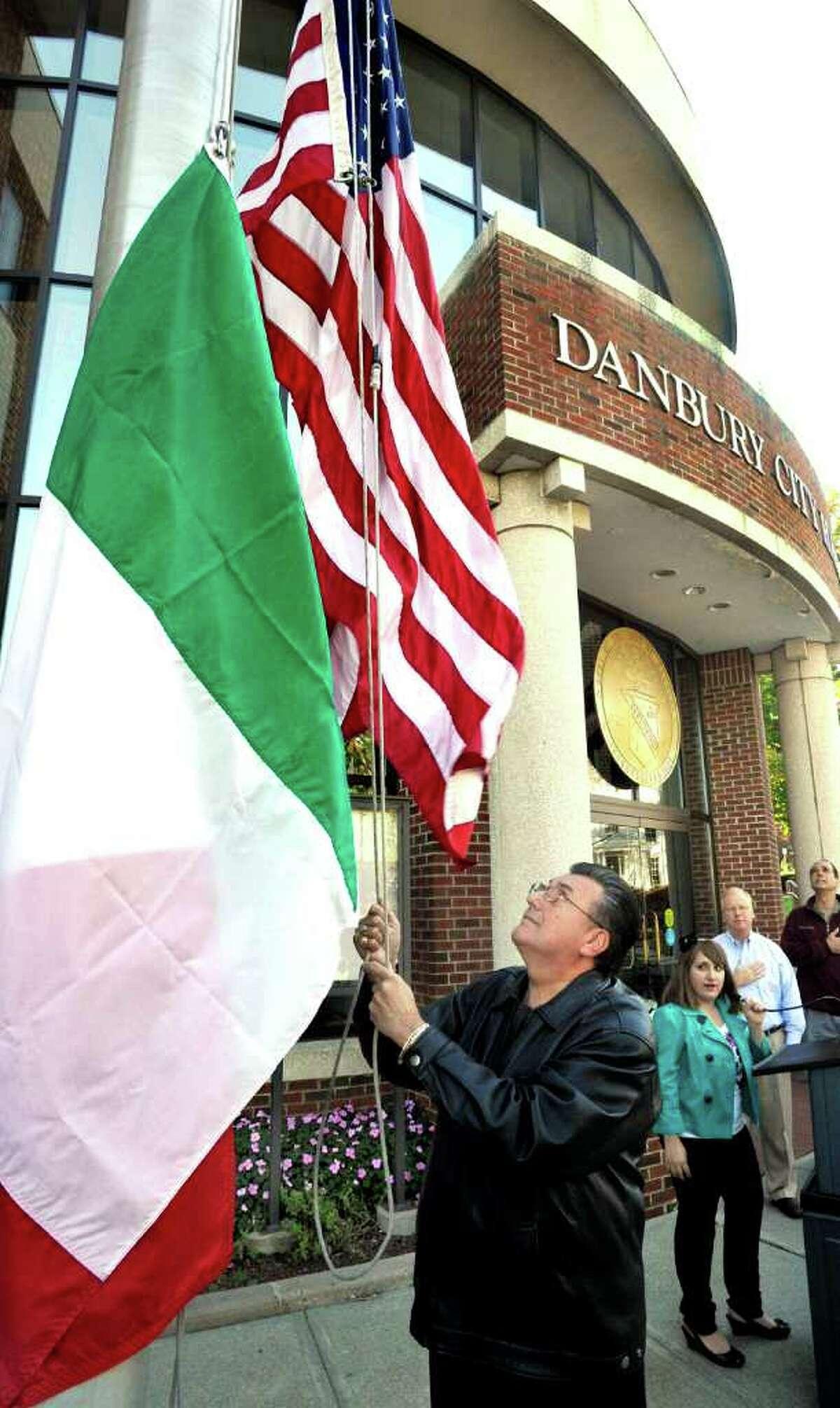 Tom Guadagno, president of the Amerigo Vespucci Lodge, raises the Italian flag outside Danbury City Hall as vocalist Maria Lostocco, 13, sings and Danbury Mayor Mark Boughton salutes, Saturday, Oct. 9, 2010.